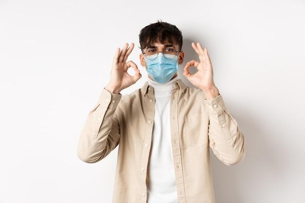 Covid-19, концепция здоровья и реальных людей. красивый парень в очках и медицинской маске, показывая одобрительный жест, рекомендую использовать профилактические меры от короны, белой стены.