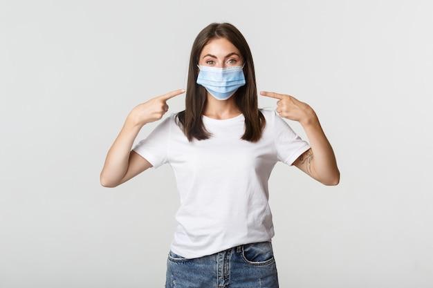 Covid-19、健康と社会的距離の概念。顔に指を指している医療マスクの魅力的なブルネットの少女、白。