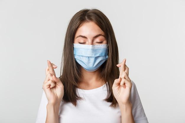 Covid-19, 건강 및 사회적 거리두기 개념. 얼굴 마스크에 희망 예쁜 여자의 클로즈업 눈을 감고 손가락 행운을 빌어 소원을 만들기.