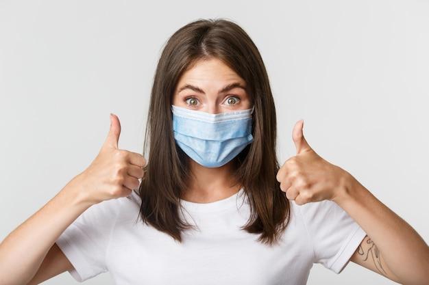 Covid-19、健康と社会的距離の概念。承認の親指を示す医療マスクの満足している魅力的な女の子のクローズアップ。
