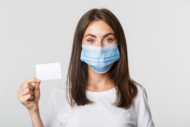 Covid-19、健康と社会的距離の概念。クレジットカードを示す、医療マスクのかわいいブルネットの少女のクローズアップ。