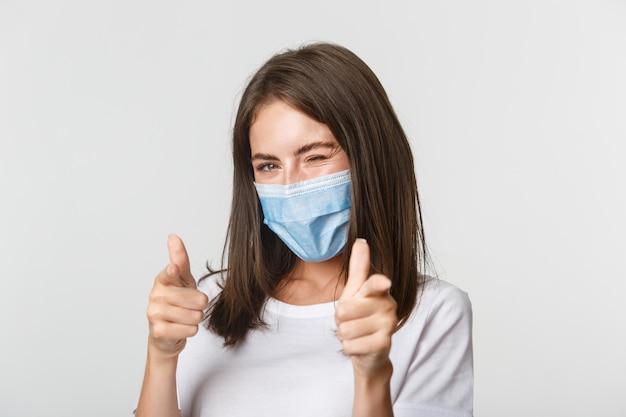 Covid-19, 건강 및 사회적 거리두기 개념. 카메라에 꼬리 치는 윙크와 손가락을 가리키는 의료 마스크에 팬티 웃는 갈색 머리 소녀.