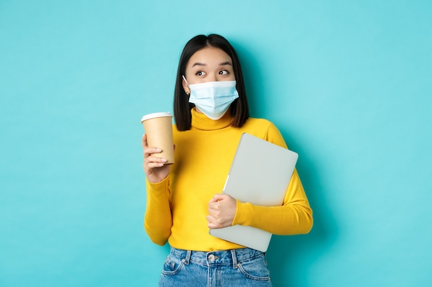 Covid-19, концепция здравоохранения и карантина. азиатская студентка в медицинской маске, стоящая с ноутбуком и кофе из кафе, стоя на синем фоне.
