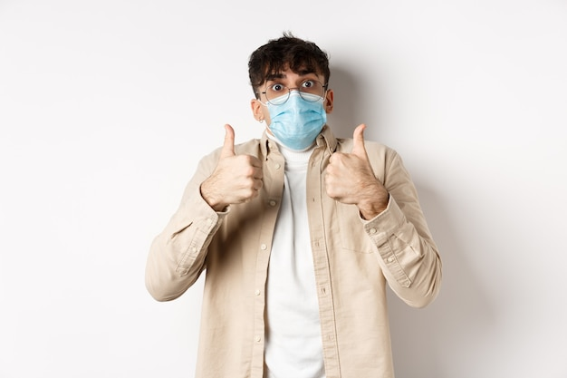 Covid-19, health and real people concept. cheerful man in glasses and sterile face mask, showing thumbs up in approval, praise and compliment product, standing on white wall.