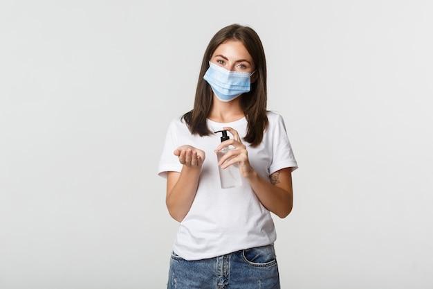 Covid-19, concetto di allontanamento sociale e sanitario. attraente giovane donna bruna in mascherina medica che applica disinfettante per le mani a portata di mano, bianco.
