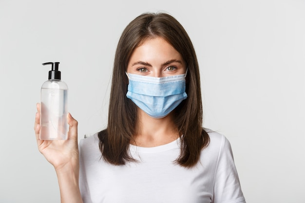 Covid-19, health and social distancing concept. close-up of attractive smiling girl in medical mask, showing hand sanitizer, recommend antiseptic.