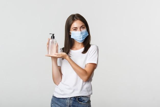 Covid-19, concetto di allontanamento sociale e sanitario. il ritratto di bella ragazza sorridente nella mascherina medica introduce il disinfettante per le mani.