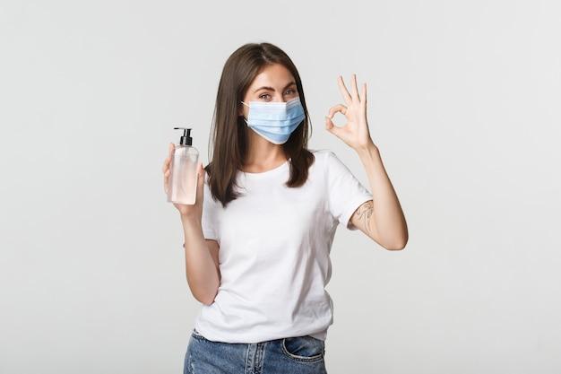 Covid-19, concetto di allontanamento sociale e sanitario. ritratto di ragazza bruna sorridente in mascherina medica, mostrando disinfettante per le mani e gesto giusto.