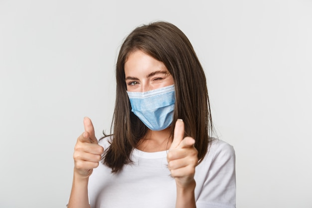 Covid-19, health and social distancing concept. sassy smiling brunette girl in medical mask winking flirty at camera and pointing fingers.