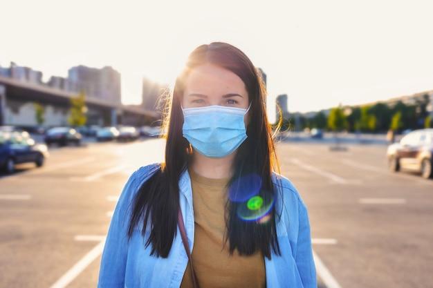 Covid-19感染の発生防止の概念。コロナウイルス。街の通りに立っている彼女の顔に使い捨て医療マスクを身に着けている若い女性の肖像画
