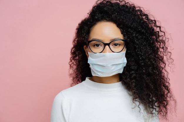 Covid-19、感染性ウイルス。ふさふさした巻き毛を持つ若い女性のショットを閉じる、透明なメガネと医療用使い捨てマスクを着用、彼女の健康を気遣って、危険な状況で保護