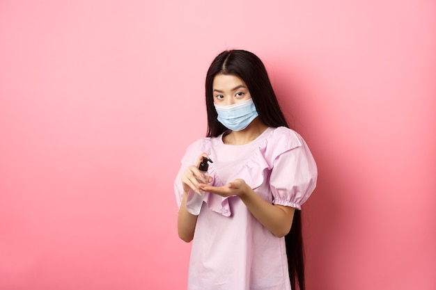 Covid-19, образ жизни и концепция здоровья. красивая азиатская женщина в медицинской маске чистит руки с дезинфицирующим средством, наносит антисептик на ладони, стоя на розовом фоне.