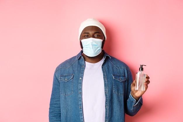 Covid-19、ライフスタイルと封鎖の概念。ピンクの背景の上に立って、消毒剤を使用して、手の消毒剤を示すフェイスマスクのハンサムな流行に敏感な男