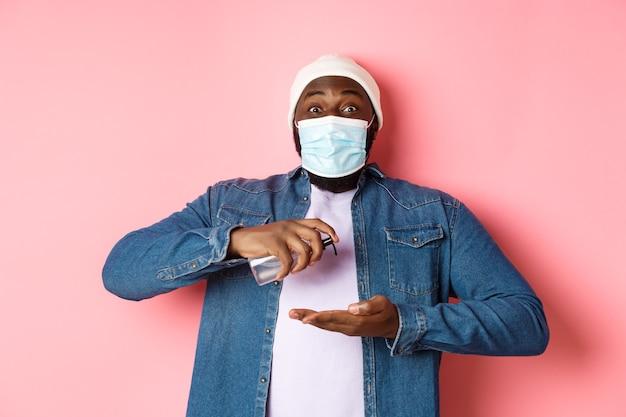 Covid-19、ライフスタイルと封鎖の概念。消毒剤で手を掃除し、消毒剤を使用し、カメラ、ピンクの背景を見てフェイスマスクで笑顔のアフリカ系アメリカ人の男。