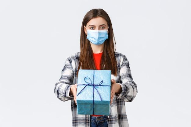 Covid-19、ライフスタイル、休日、お祝いのコンセプト。医療マスクストレッチ手で陽気な若い女の子、あなたに誕生日プレゼントを渡す、笑顔、b-day、白い背景で祝福します。