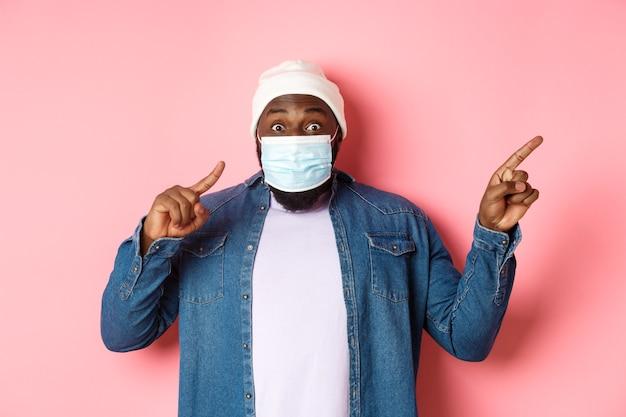 Covid-19, stile di vita e concetto di blocco. impressionato uomo nero in maschera facciale che mostra annuncio, indicando a destra il promo e fissando la telecamera stupito, sfondo rosa.