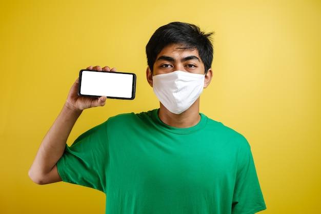 Образ жизни covid-19, эмоции людей и досуг на концепции карантина. возбужденный молодой азиатский парень в медицинской маске показывает пустой белый экран смартфона, выглядит удивленным