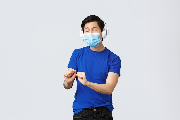 Covid-19ライフスタイル、人々の感情、検疫コンセプトの余暇。家で一人で目を閉じて踊る面白い屈託のないアジアの男、ヘッドフォンで音楽を聴く、医療用マスクを着用