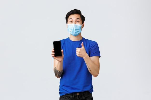 Образ жизни covid-19, эмоции людей и отдых на концепции карантина. счастливый довольный азиатский парень рекомендует скачать новое приложение или посетить интернет-магазин, показать большой палец вверх и мобильный экран