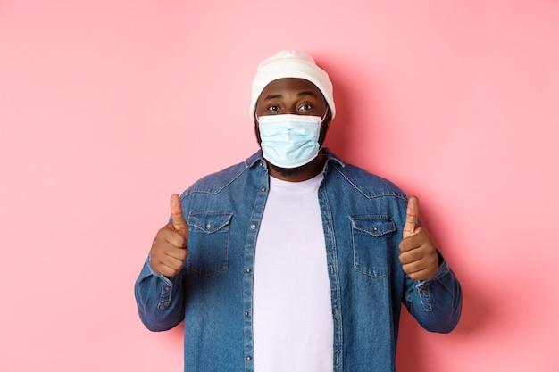 Covid-19, stile di vita e concetto di quarantena. soddisfatto uomo di colore con maschera facciale che mostra il pollice in su, in piedi su sfondo rosa