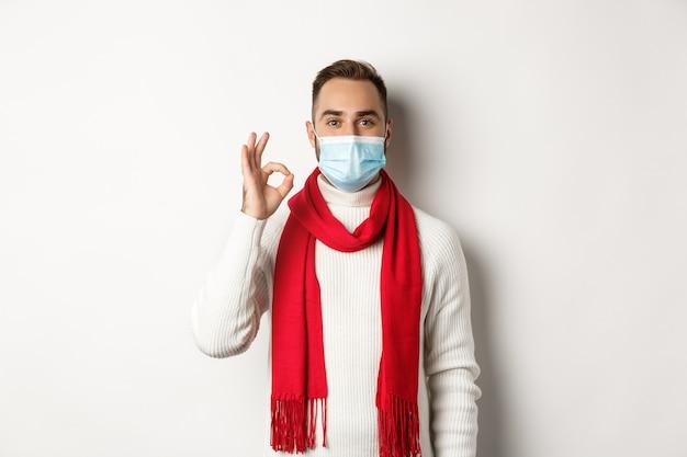 코비드-19, 잠금 및 검역 개념. 흰색 배경처럼 확인 표시, 승인 또는 동의를 보여주는 얼굴 마스크에 만족한 잘생긴 남자
