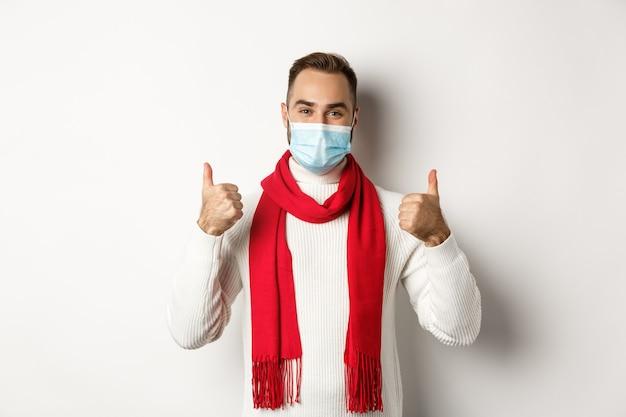 코비드-19, 잠금 및 검역 개념. 웃는 남자는 얼굴 마스크를 쓰고 엄지손가락을 치켜들고 코로나바이러스로부터 자신을 보호하고 흰색 배경 위에 서 있습니다.
