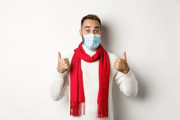 코비드-19, 잠금 및 검역 개념. 흰색 배경에 스웨터와 빨간 스카프에 서 있는 엄지손가락을 보여주는 얼굴 마스크에 놀란 남자