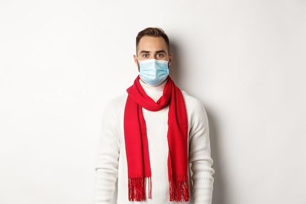 코비드-19, 잠금 및 검역 개념. 겨울 스웨터와 흰색 배경에 의료 마스크 서 있는 젊은 남자.