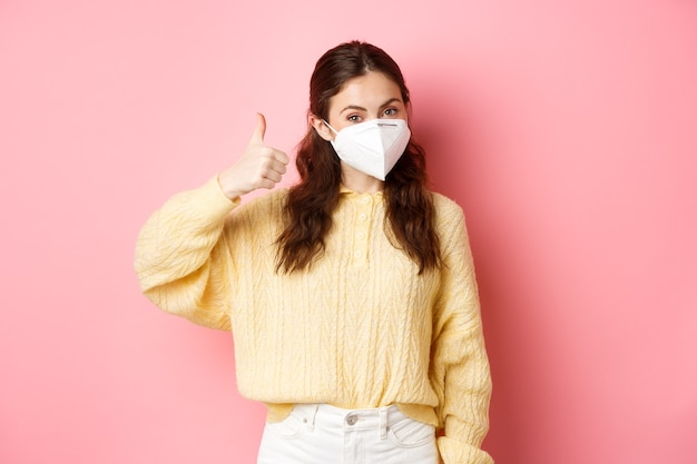 Covid-19, lockdown and pandemic concept. cheerful brunette girl wears medical respirator to prevent coronavirus, shows thumbs up and nod, say yes, stands against pink wall.