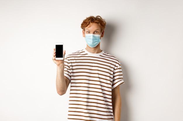 Covid-19, 온라인 의사 개념. 흰색 배경 위에 서 스마트 폰 화면을 보여주는 얼굴 마스크에 빨간 머리 남자를 웃 고.