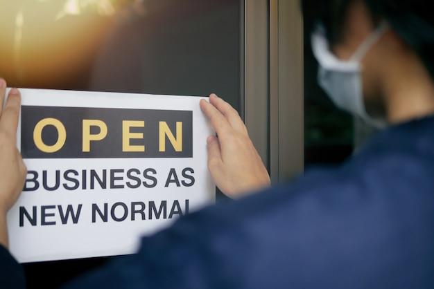 新規のコロナウイルスcovid-19パンデミックにおいて、ビジネスの再開は新しい正常に適応します。ドアにオープンサインopen business as new normalを置いた医療用マスクを身に着けている事業主の背面図。