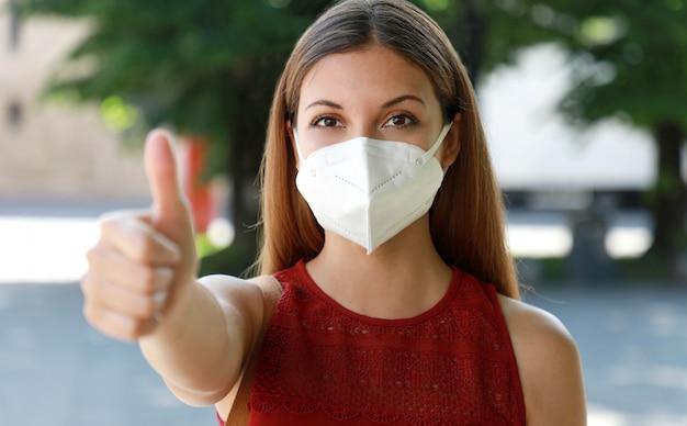 Covid-19 оптимистичная девушка в защитной маске ffp2, избегающая коронавирусной болезни 2019, показывает палец вверх на городской улице