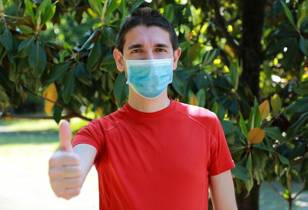 Covid-19 optimistic sporty man wearing surgical mask on face during pandemic coronavirus disease showing thumbs up in city park