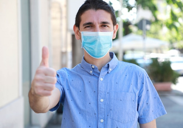 Covid-19 optimistic young man wearing surgical mask on face during pandemic coronavirus disease showing thumbs up in city street