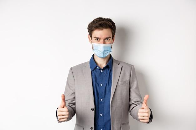 Covid-19、パンデミックおよびビジネスコンセプト。スーツと医療マスクの陽気な男がオフィスで予防措置を使用して、親指を立てて、白い背景を表示します。
