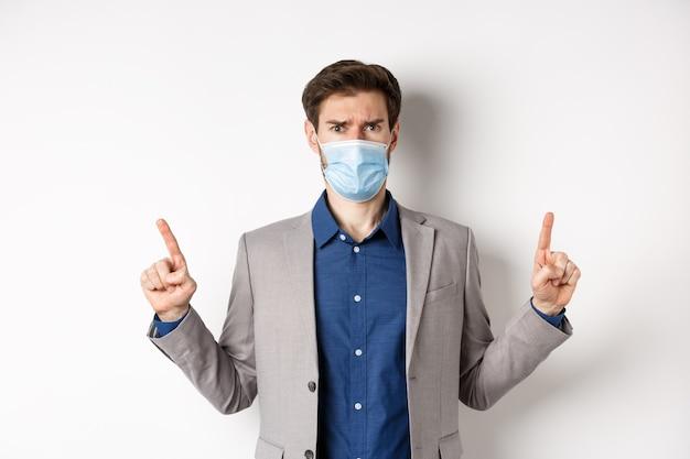 Covid-19, 유행성 및 비즈니스 개념. 불공정 한 상황, 흰색 배경에 대해 불평, 양복과 의료 마스크 가리키는 손가락에 실망 찡그림 남자.