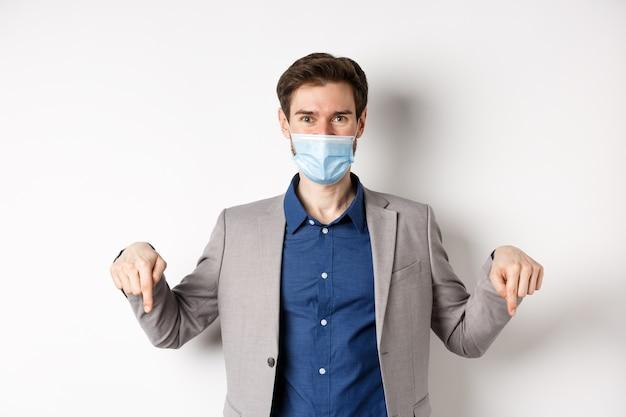 Covid-19, 유행성 및 비즈니스 개념. 의료 마스크와 양복, 아래로 손가락을 가리키고 회사 로고, 흰색 배경을 보여주는 잘 생긴 사업가.