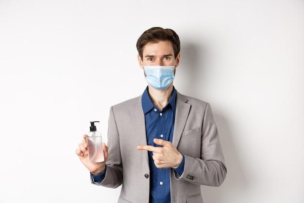 Covid-19、パンデミックおよびビジネスコンセプト。手指消毒剤のボトルを指して、職場で消毒剤を使用して、白い背景の医療マスクのサラリーマン。