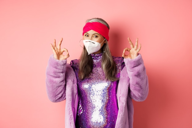 Covid-19, 유행병 및 패션 개념. 멋진 디스코 드레스와 인공 호흡기를 착용하고 괜찮은 징후를 보이고 얼굴 마스크를 착용하고 분홍색에 사회적 거리를 두도록 요청하는 멋진 아시아 할머니.