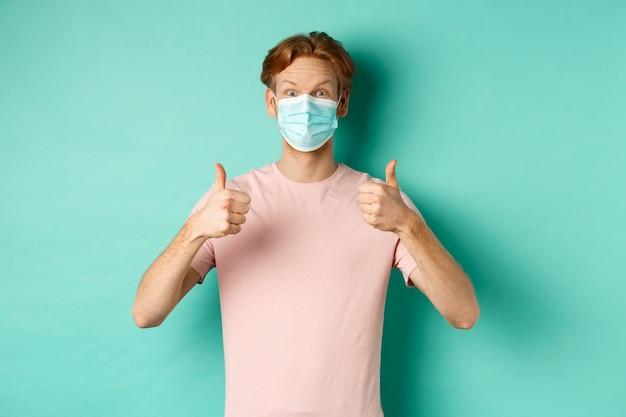 Covid-19, 유행병 및 라이프 스타일 개념. 청록색 배경 위에 서있는 승인, 찬양 제품에 엄지 손가락을 보여주는 의료 마스크에 쾌활한 빨간 머리 남자.