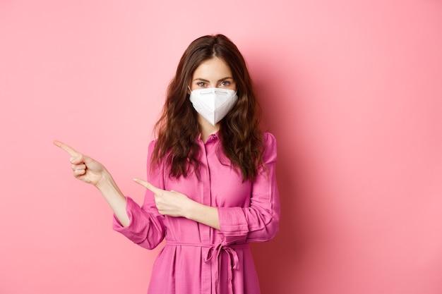Covid-19, 유행병 및 라이프 스타일 개념. 얼굴 인공 호흡기에 세련 된 현대 소녀, 왼쪽 손가락, copyspace 옆으로 표시, 분홍색 벽에 서 서.