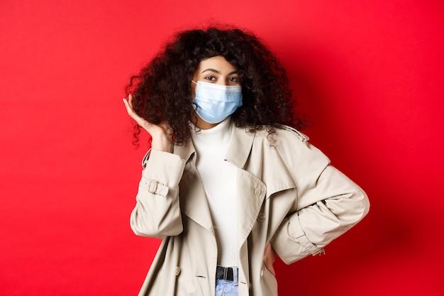 Covid-19, 유행병 및 격리 개념. 의료 마스크와 트렌치 코트에 세련 된 coquettish 여자, 그녀의 곱슬 헤어 스타일을 고정 하 고 웃 고, 빨간색 배경.