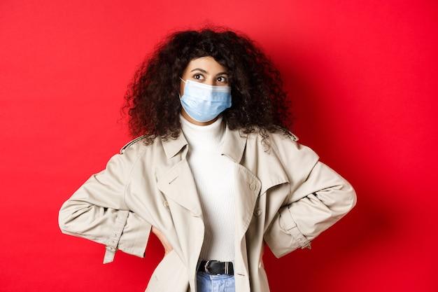 Covid-19, 유행병 및 격리 개념. 의료 마스크와 트렌치 코트에 세련 된 열정적 인 여자 웃 고 왼쪽 상단 모서리, 빨간색 배경보고.
