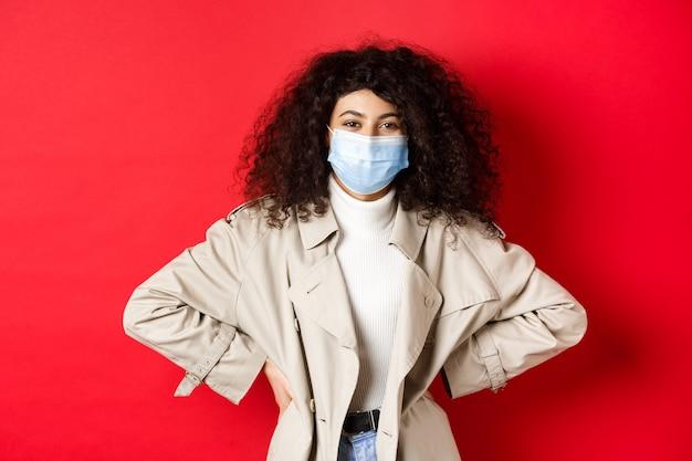 Covid-19, 유행병 및 격리 개념. 트렌치 코트와 의료 마스크를 쓰고 곱슬 머리를 가진 세련 된 현대 여성, 미소를 카메라, 빨간색 배경.