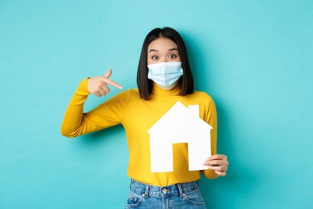 Covid-19, 유행성 및 부동산 개념. 쾌활 한 아시아 여자 의료 마스크에 웃 고, 종이 집 컷 아웃을 보여주는, 속성, 파란색 배경 구매 대행사를 추천합니다.