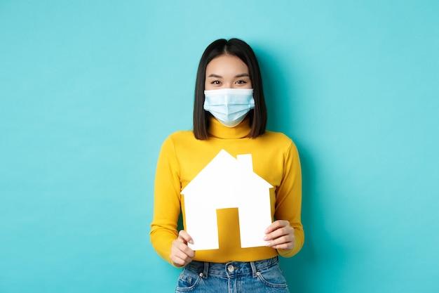 Covid-19、パンデミックおよび不動産の概念。医療マスクで笑って、紙の家の切り抜きを示して、プロパティを購入するための代理店をお勧めします、青い背景の陽気なアジアの女性