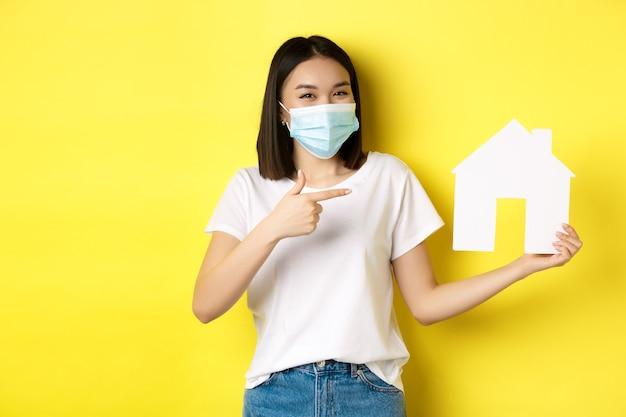 Covid-19, 유행성 및 부동산 개념. 의료 마스크에 웃 고, 종이 집 컷 아웃을 보여주는 쾌활 한 아시아 여자는 재산을 구입을위한 기관을 추천합니다.