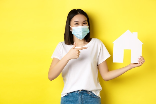 Covid-19、パンデミックおよび不動産の概念。医療マスクで笑って、紙の家の切り抜きを見せて、陽気なアジアの女性は、プロパティを購入するための代理店をお勧めします。