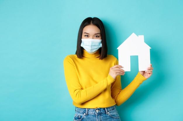 Covid-19, 유행성 및 부동산 개념. 파란색 배경 위에 서있는 코로나 바이러스 동안 의료 마스크를 쓰고 종이 집 컷 아웃을 보여주는 노란색 옷에 젊은 아시아 여자.