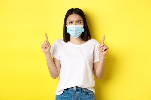 Covid-19、パンデミックおよび社会的距離の概念。医療マスクで失望したアジアの女の子、眉をひそめているとロゴに指を指して、黄色の背景の上に立っている
